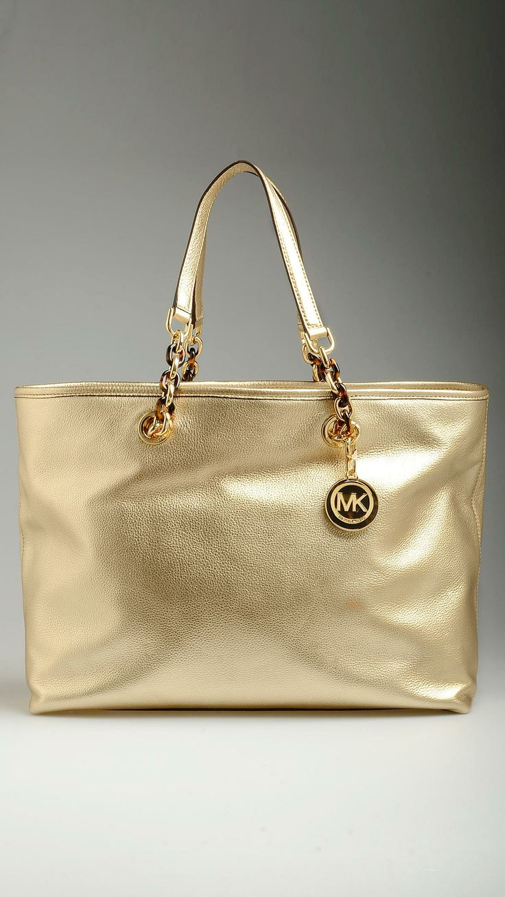 Pale gold tan Saffiano Cynthia shopping bag featuring snap flap top, zippered compartment, monogram lining, four inner open pockets and a zippered pocket, golden and tortoise-acetate embellished handles, tote handles, protective studs, MK key-chain detail, 15.7'' x 5.5'' x 11'', 100% tan Saffiano.