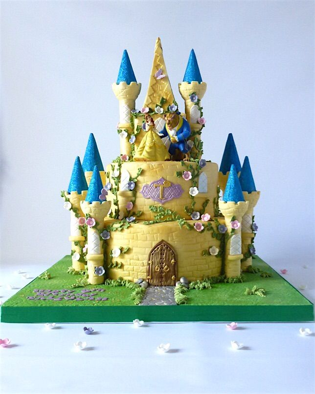 """Beauty and the Beast Fairy Castle cake  Sometimes I make a cake that makes me want to be a little girl again and this was one of those times! It was a real stunner, the finished cake stood an impressive 2 feet tall and was displayed on a 20"""" board, it had 8 towers all topped with royal blue glittered roofs, pretty sugar blossom and lots of sparkle. Although this one was themed to beauty and the beast we could adapt the design any princess theme."""