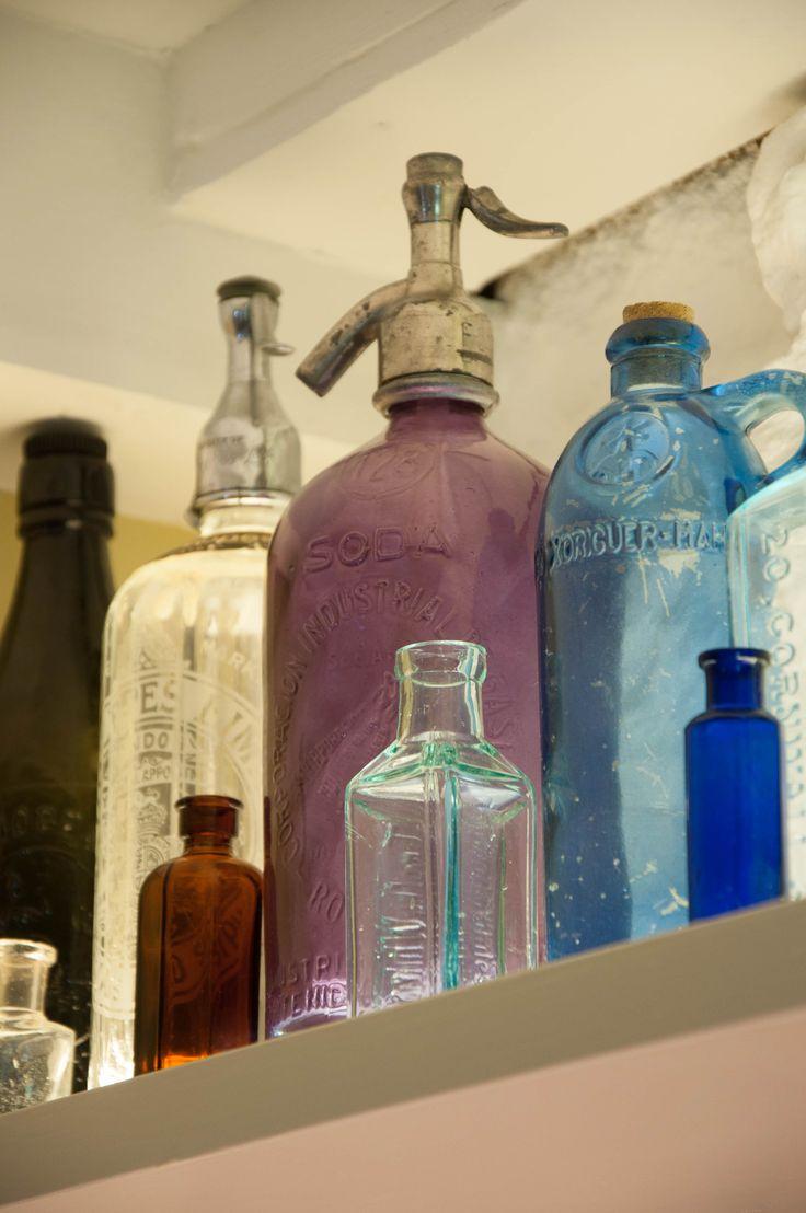 Colourful glass syphon bottles on illuminated shelf