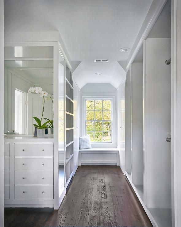 White walk in closet features a nook filled with a built-in dresser with inset drawers under a mirror facing a wall of stacked tension rod clothes rails.