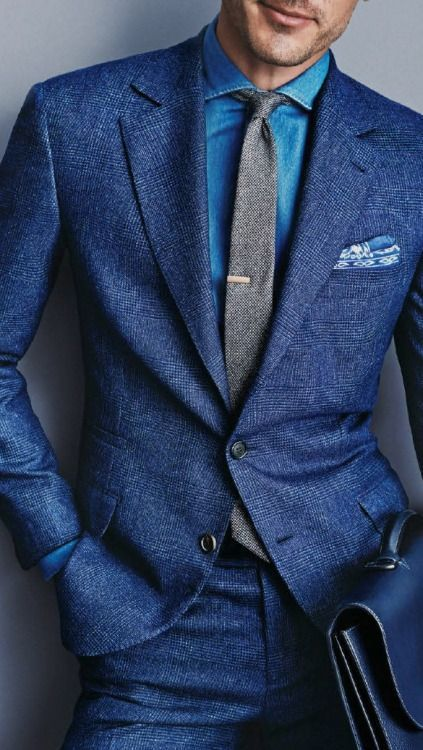 Shop this look on Lookastic: http://lookastic.com/men/looks/denim-shirt-tie-suit-pocket-square-briefcase/9423 — Blue Denim Shirt — Grey Wool Tie — Blue Wool Suit — Blue Print Pocket Square — Blue Leather Briefcase