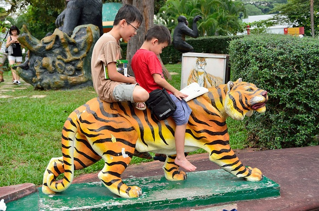 Kids reading a book on a tiger statue.    If you want to see a lot of pictures taken in Haw Par Villa, have a look at my gallery.     see all children movies here click to see