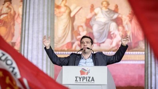 Alexis Tsypras bei seiner Siegesrede. Vor ihm wird die Flagge der sozialistischen Partei Italiens geschwenkt. Quelle: dpa