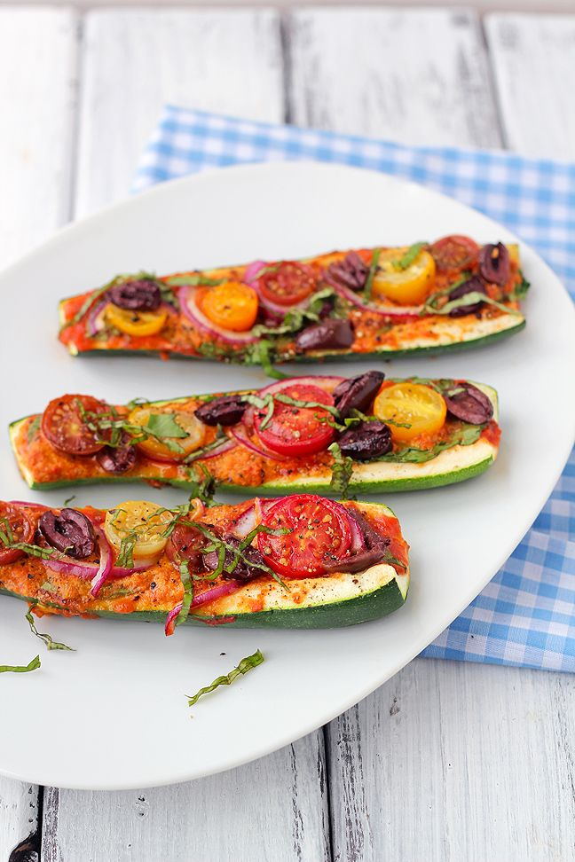 Vegan Zucchini Pizza Boats | Fresh zucchini is cut lengthwise and filled with a cheesy marinara sauce made with nutritional yeast.  The zucchini is topped with a variety of vegetables including tomatoes, olives, onions, and fresh basil.