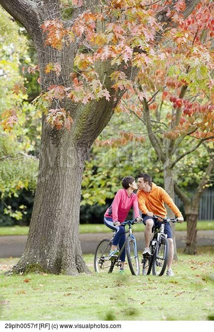 Man and woman cycling in park kissing