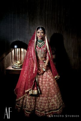 Bridal Lehengas - Karthik & Upasana wedding story | WedMeGood | Bride in a Dark Pink Lehenga with Golden Embroidery and Emerald Jewelry  #wedmegood #indianbride #indianwedding #bridal #lehenga #gold #pink #jewelry #indianjewelry