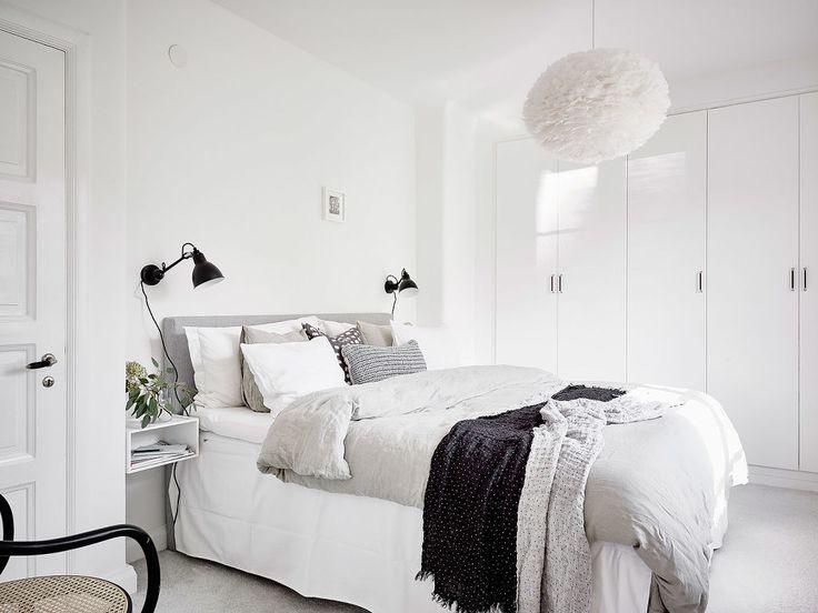 Vit sängkappa, svarta lampor, blanka garderobsdörrar, grått golv