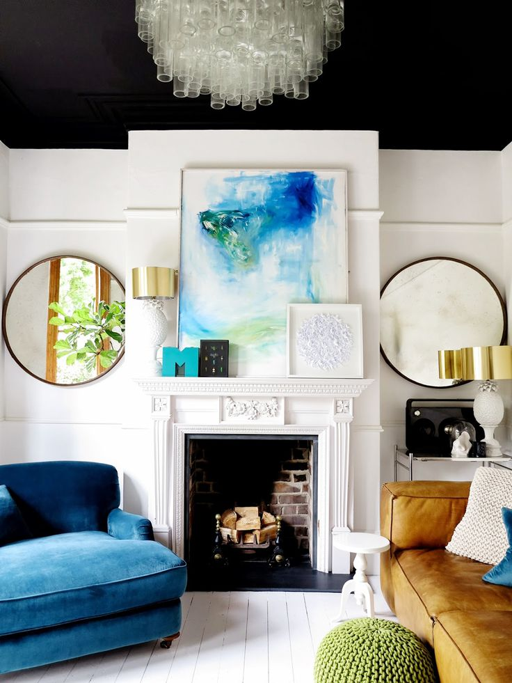 Abstract art above the fireplace in black-and-white living space