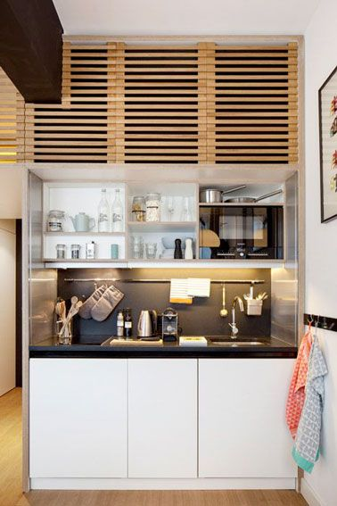 Une kitchenette bois monobloc avec une crédence noire