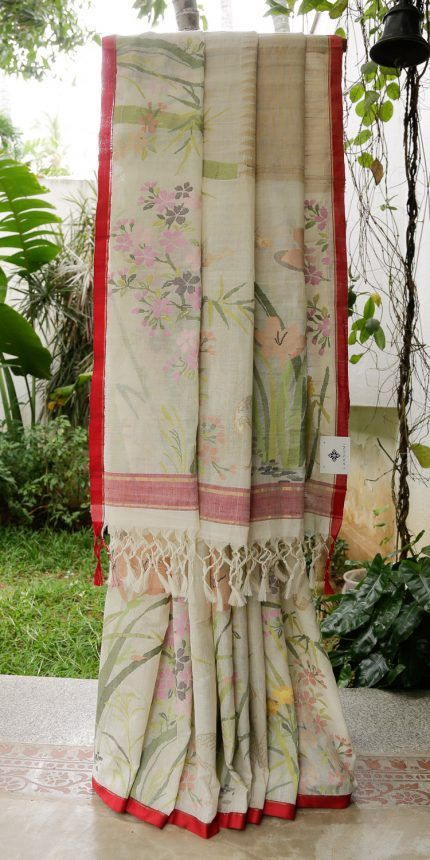 This khadi sari is in daisy white and bone white with jamdani work all along. The border is in sangria red and gold zari and the pallu is in daisy white with jamdani work and a band of sangria red …