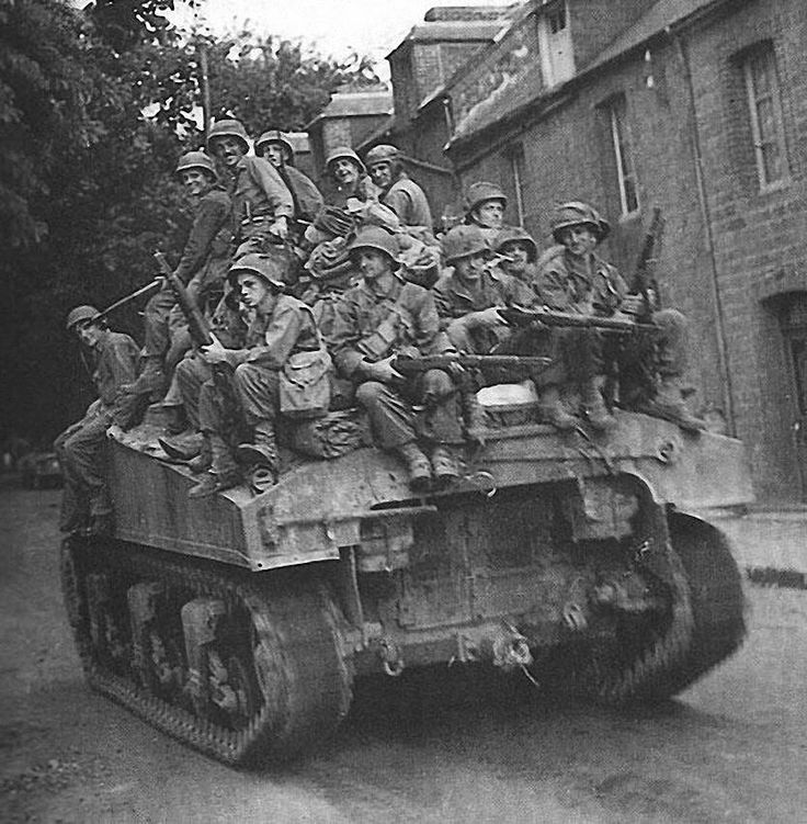 A squad of infantrymen from First Army catch a ride on an M4 Sherman Tank as they moved through the French town of La Ferte-Mace, 14 August 1944.  Note: Probably a tank from 745th Tank Battalion. Soldiers are from 3rd Battalion, 16th Infantry Regiment, 1st Infantry Division.