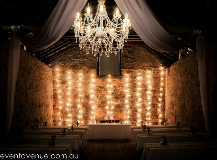 Romatic wedding festoon barn lighting on stone bricks with chandelier and draping to soften the look.
