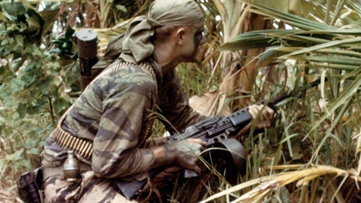 This familiar photo shows a U.S. Navy SEAL on a mission early in the war. He's got the standard drum magazine loaded on his Stoner 63 with several belts of extra ammunition draped over his shoulders.