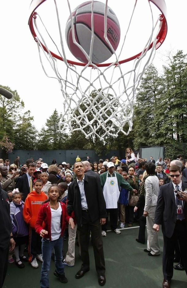 President Barack Obama watches a girl shoot a basketball as part of the Annual Easter Egg Roll on the South Lawn at the White House in Washington, April 13, 2009.