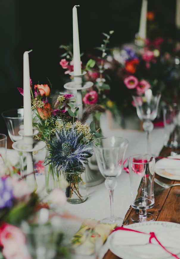 Reception Table Arrangements - mixed bright berry tones in mismatched glasses