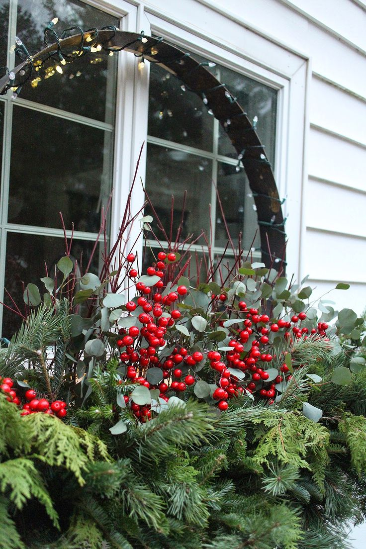 Holiday window box with greens, dogwood twigs, silver dollar eucalyptus, faux berries.