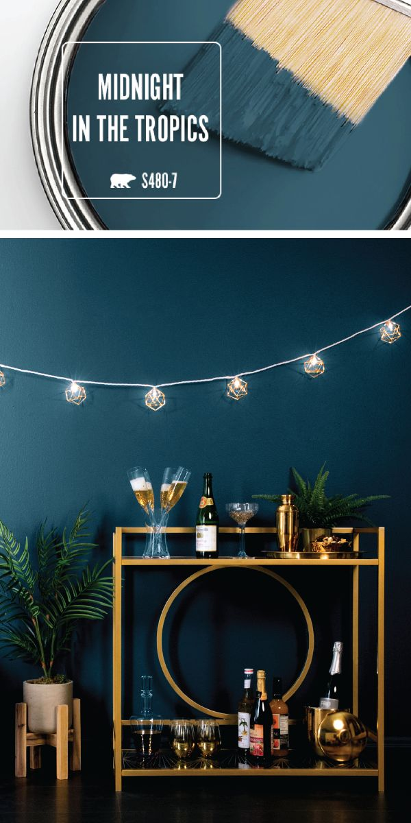 Kick 2018 off on a stylish note with the dark blue hue of Midnight In The Tropics by BEHR Paint. This deep shade of navy adds a bold, sophisticated style to the interior design of your home. A retro gold bar cart and string lights are all you need to recreate this elegant New Year's Eve party set-up in your living room. Check out the full article for more home decor inspiration. #retrohomedecor