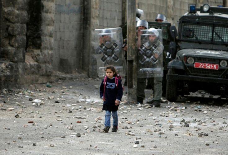 Shuafat, Gerusalemme. Una bambina palestinese passa davanti a un blocco israeliano quotidianamente per andare e tornare da scuola