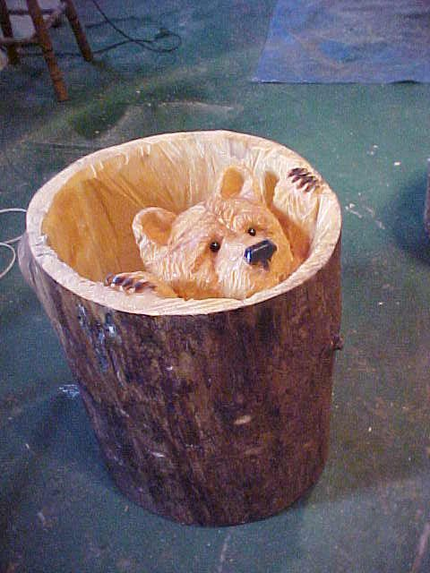 Bear carved inside a White Pine Log, and a round glass table top can be put on top.    - Chainsaw carved art by Rick Pratt