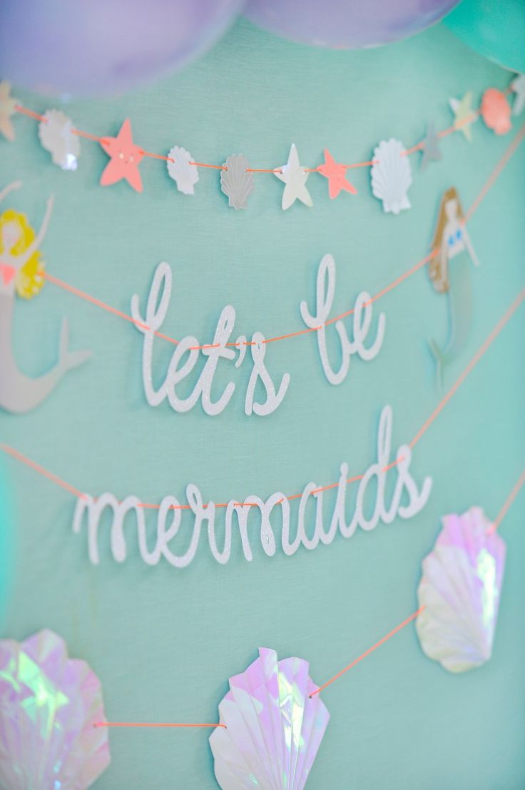 """Decorate a simple wall with party garland. This Meri Meri """"Lets Be Mermaids"""" garland adds so much to the mermaid birthday party theme. Mermaid Party styling by Happy Wish Company. Photography by Tammy Hughes Photography. Stationery by Minted artist, Bonjour Paper."""