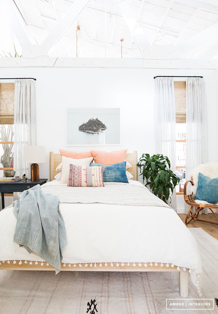 Bright white bedroom with exposed ceiling beams and bohemian décor