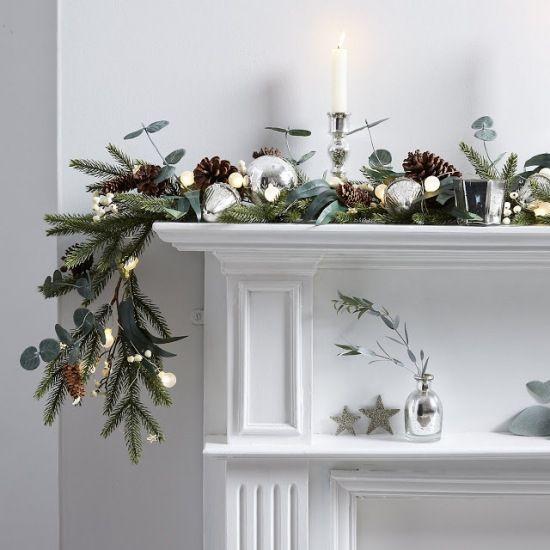 pomysł na świąteczną zieloną girlandę z brązowymi szyszkami i świecznikami na portal kominkowy - Lovingit.pl