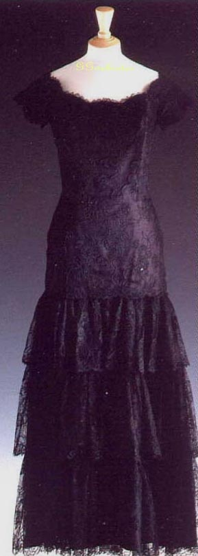 Victor Edelstein designed this black lace off-the-shoulder style dress which covers a magenta pink silk underskirt. This gown is one of Diana's very feminine early styles. Her usual accessory with this gown was a long string of faux pearls. She wore it on a visit to Hamburg Germany for a banquet in November 1987. Also in 1987, Diana wore it to Festival Hall in London, covering it with a velvet cape. Lot #56 raised $ 25,300 for Diana's charities.