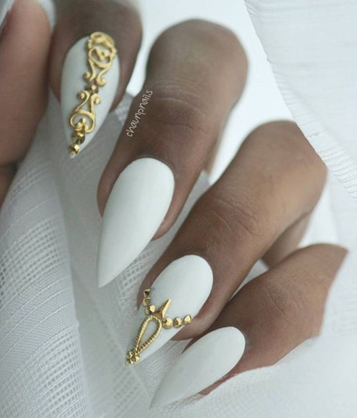 Beautiful dramatic white stiletto nails with gold embellishments.