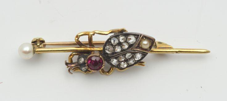 Een geelgouden met zilveren 'kever'-broche, lichaam kever bezet met diamanten, robijn en parel, broche-pen bekroond door parel, vermoedelijk einde 19e eeuw