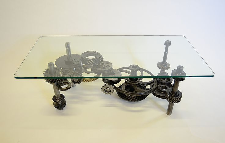 "The ""Gears Table"" (16 1/2"" x 48"" x 24"") is fabricated out of 35 industrial gears in steel, stainless steel and brass by Los Angeles metal sculptor Bruce Gray. This stunning and unique heavy duty table is constructed with hidden welds to make it look like it could almost function in some unexpected way. SOLD! Contact the Bruce to find out about ordering your own steampunk gears table. Price: Approximately $6000 depending on size and complexity. Glass top: 2'x4' and base only is (16x39x20"")."