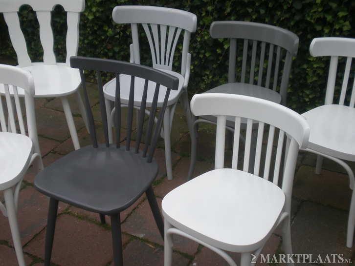 Verschillende houten stoelen voor in de keuken aan een lange tafel