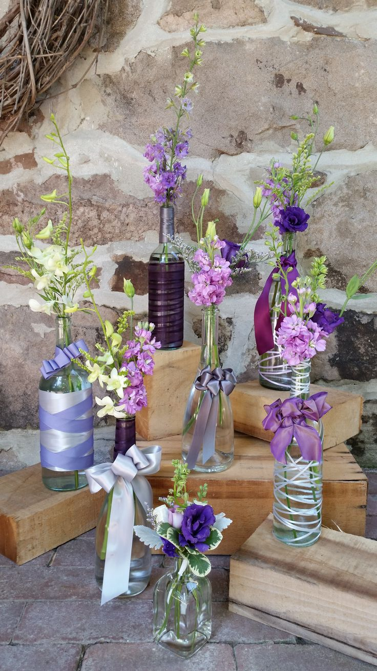 Blossom Bliss Florist Wedding Centerpieces: Reclaimed wine bottles+purple  flowers