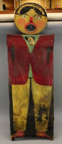 """CARNIVAL BALL TOSS FIGURAL  c. 1930's, hand painted canvas body and wood face, exaggerated mouth opening used to toss ball through and win a prize, quite primitive detail, a great early folk art example, probably used at the local fair. 56"""" h."""