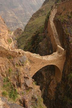 El puente Shahara en Yemen. Esta maravilla de la ingeniería extiende un profundo cañón de escarpados 300 pies. Construido a principios del siglo XVII, este famoso puente ha superado la prueba del tiempo. De ambos lados del puente las montañas separaron y revelaron una visión del enorme valle. El puente hay que cruzar para acceder a la ciudad de fortaleza de montaña de Shahara y sus hermosos bancales.