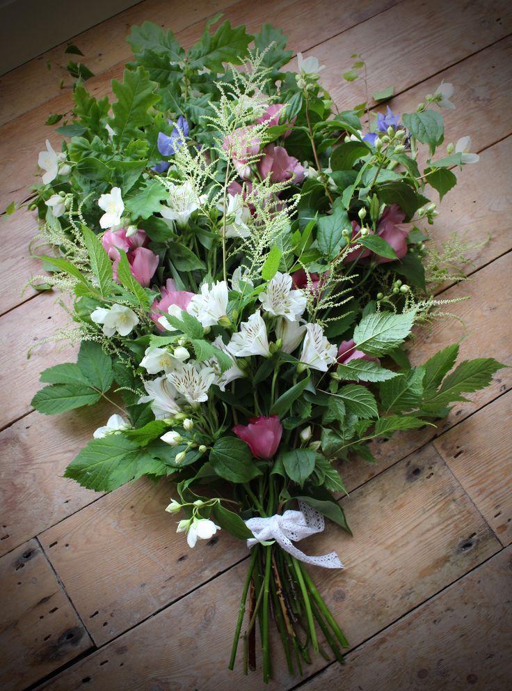 Seasonal British flowers arranged in a natural funeral sheaf.  Orange blossom, aruncus, alstroemeria, iris, lisianthus and oak leaves.  Tuckshop Flowers, Birmingham.