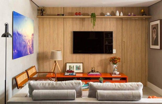 No apartamento da designer de interiores Melina Romano e do seu marido Victor, a sala de tv ganhou diversos tipos de iluminação. Painel de carvalho, que camufla a porta que leva à área íntima e ajuda a aquecer o ambiente, rack com acabamento de laca na c (Foto: Edu Castello/Editora Globo)