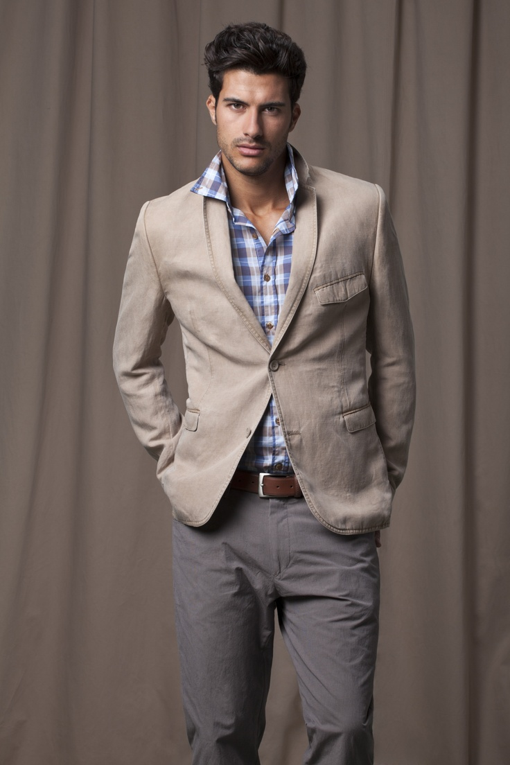 Grey casual trouser, blue checked shirt, brown belt and beige blazer with chest pocket