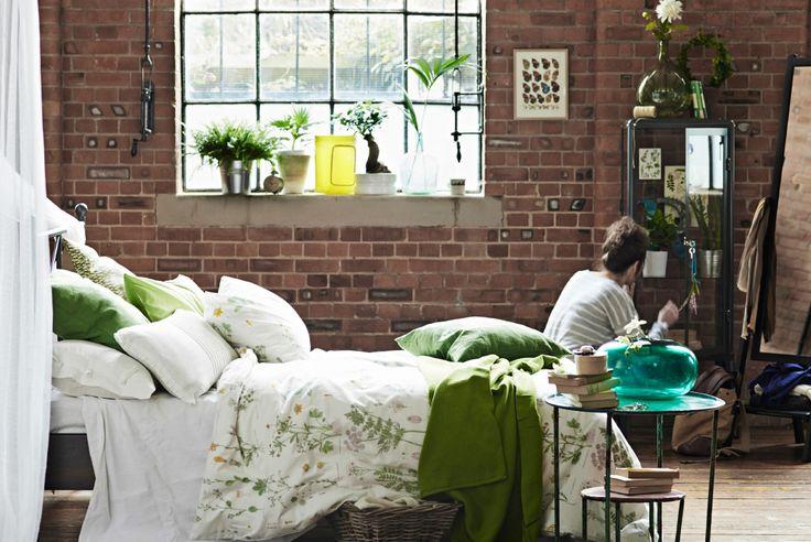 Vista de un dormitorio con una cama llena de cojines, ropa de cama con motivos botánicos, primer plano de una mesilla de noche y una vitrina de fondo. Fila de plantas en un alféizar.