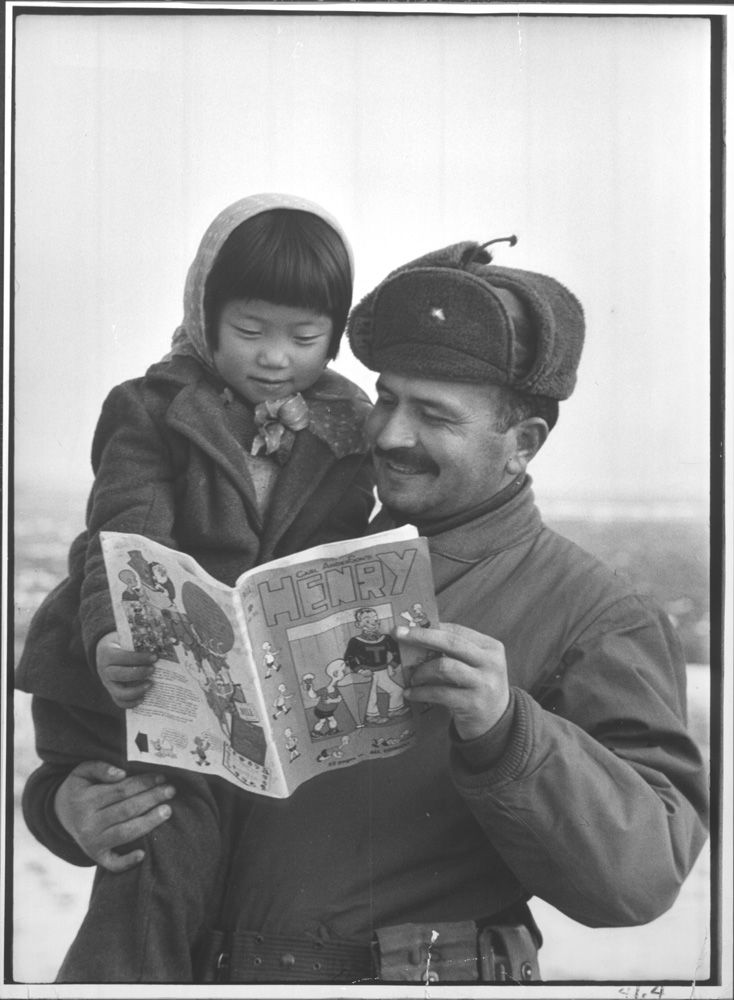 A Turkish soldier and a young girl look at an American comic book during the Korean War, 1951.