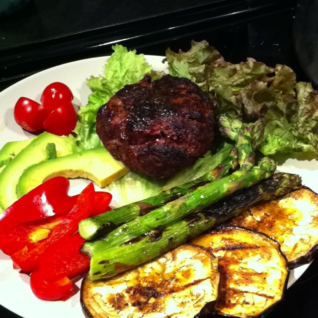 Grass-fed beef w/ lettuce bun and grilled veggies Grilled eggplant and asparagus on BBQ  Burger seasoning-onions, garlic, tamari,turmeric, cumin, hot sauce, s & p  Garnished with organic red peppers, avocado and cherry tomatoes and lemon/ oil dressing.