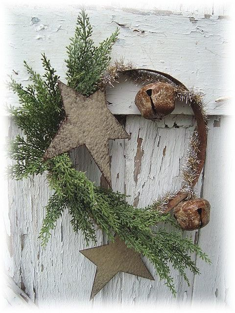 Prim wreath... a rusty metal ring...with dried greens, rusty stars and jingle bells....  sooo cool!   :)