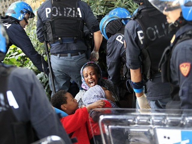 "Italian police officers surround a family of migrants during an operation to remove them from the Italian-French border in the Italian city of Ventimiglia on June, 16, 2015.  Italy and France engaged in a war of words as a standoff over hundreds of Africans offered a graphic illustration of Europe's migration crisis. Italian Interior Minister Angelino Alfano described images of migrants perched on rocks at the border town of Ventimiglia after being refused entry to France as a ""punch in the…"
