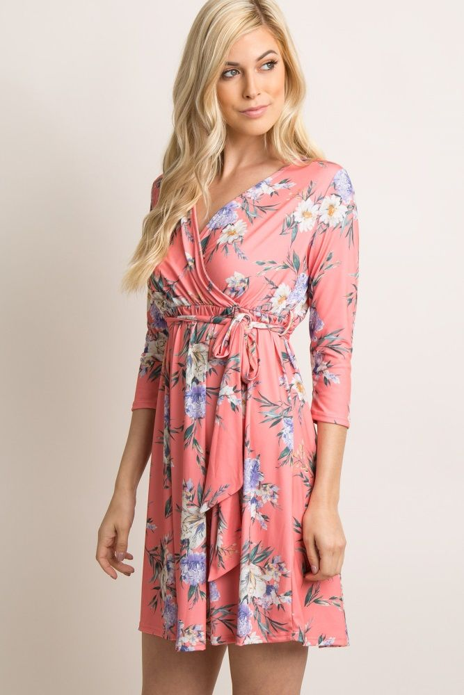 A bright hued, palm and floral print dress featuring a wrap front style with a v-neckline, a cinched elastic waistline with a sash tie and 3/4 sleeves. This style was created to be worn before, during, and after pregnancy.