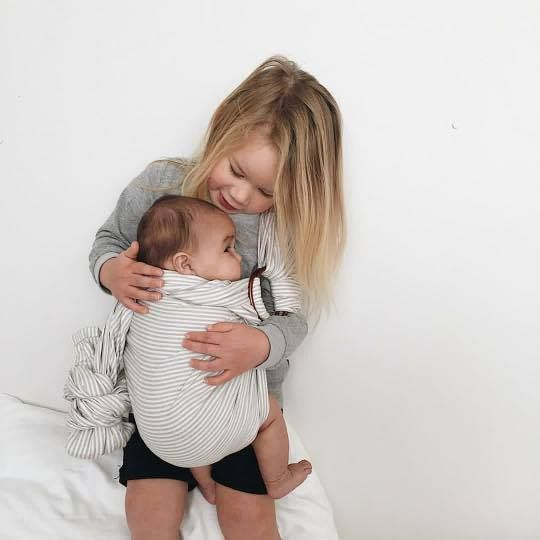 Anneke's second baby holding her fourth baby in our Grey Stripe Ring Sling @hush_babydesign