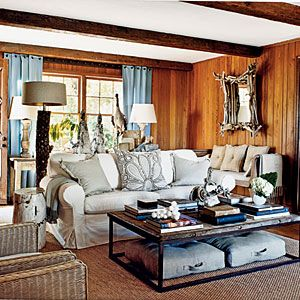 now this is how you take a room with dated dark panelling and brighten it up - lighten the ceiling, light upholstery, light lamp shades, light textured mirror, bright drapes, coffee table not too dark and airy visually - from CoastalLiving.com