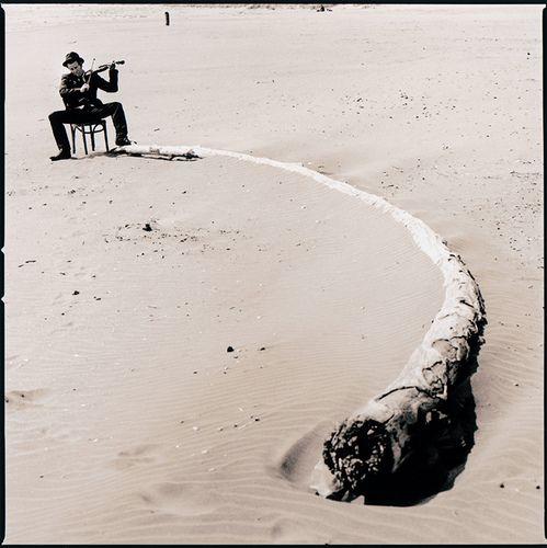 Tom Waits By Anton Corbijn - Anton Corbijn (1955) is een Nederlands fotograaf, die bekend is geworden door zijn foto's van vooral rock- musici en andere artiesten. Tevens is hij grafisch ontwerper, doet hij de art direction en regie voor videoclips en ontwerpt decors voor popconcerten van onder andere Depeche Mode. Ook is hij bekend als regisseur van speelfilms, waarvoor hij meerdere prestigieuze prijzen in ontvangst heeft mogen nemen.