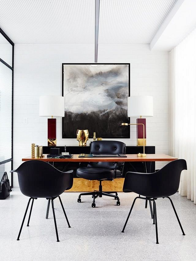 A workspace with large art, black chairs, and gold accents