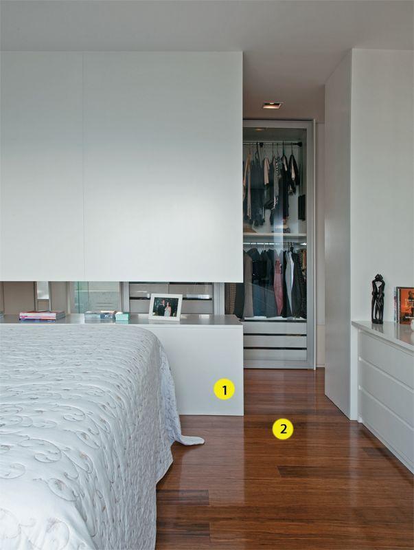 Quarto 1. 1. De madeira laqueada branca, o fundo do armário (Marcenaria Trettel) divide o quarto do closet. O rasgo de 45 cm de altura entre as partes inferior e superior permite a passagem de luz natural e cria um apoio para objetos