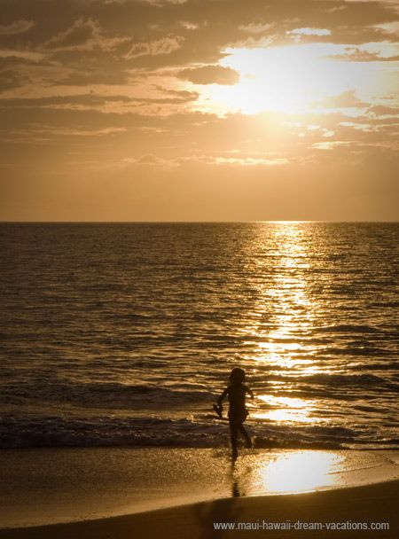 A young girl is playing on the beach as the sun sets on Makena, Maui Hawaii.