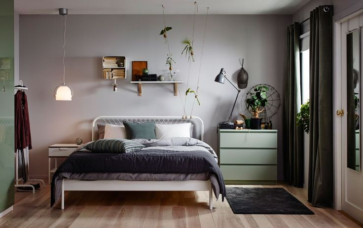 A small bedroom furnished with a bed for two in white metal with square patterned metal bars in the headboard. Shown together with a white bedside table on one side and a green chest of drawers on the other.
